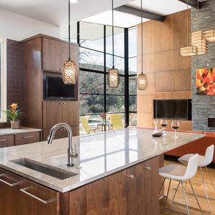 オースティンの大きいコンテンポラリースタイルのおしゃれなキッチン (アンダーカウンターシンク、フラットパネル扉のキャビネット、茶色いキッチンパネル、サブウェイタイルのキッチンパネル、中間色木目調キャビネット、珪岩カウンター、無垢フローリング、シルバーの調理設備の、茶色い床) の写真