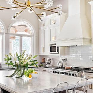 Ejemplo de cocina en U, clásica, extra grande, con fregadero bajoencimera, armarios estilo shaker, puertas de armario blancas, encimera de mármol, salpicadero blanco, salpicadero de azulejos tipo metro, electrodomésticos de acero inoxidable, suelo de ladrillo y una isla