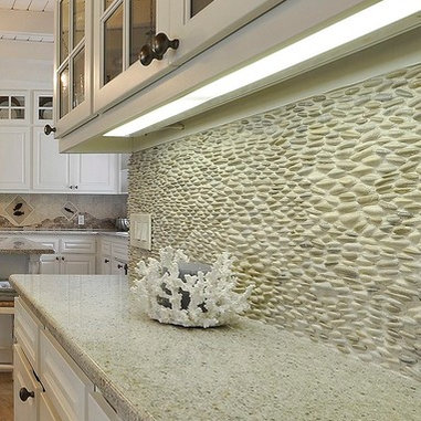 river rock backsplash has become a favorite in this lake house kitchen