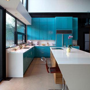 Diseño de cocina moderna, abierta, con armarios con paneles lisos, puertas de armario azules, encimera de cuarzo compacto, salpicadero blanco, electrodomésticos con paneles y fregadero bajoencimera