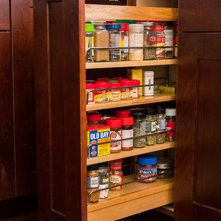シカゴの中くらいのミッドセンチュリースタイルのおしゃれなキッチン (シングルシンク、シェーカースタイル扉のキャビネット、クオーツストーンカウンター、青いキッチンパネル、ガラスタイルのキッチンパネル、シルバーの調理設備、無垢フローリング、赤い床、白いキッチンカウンター) の写真