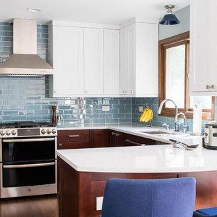 シカゴの中サイズのミッドセンチュリースタイルのおしゃれなキッチン (シングルシンク、シェーカースタイル扉のキャビネット、クオーツストーンカウンター、青いキッチンパネル、ガラスタイルのキッチンパネル、シルバーの調理設備の、無垢フローリング、赤い床、白いキッチンカウンター) の写真