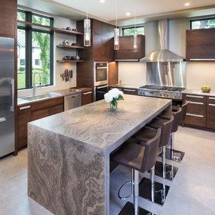 Ispirazione per una cucina minimalista di medie dimensioni con ante lisce, top in pietra calcarea, paraspruzzi beige, elettrodomestici in acciaio inossidabile, pavimento in cemento, isola e ante in legno bruno