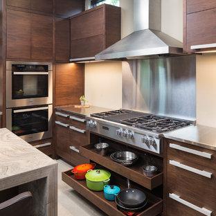 Diseño de cocina moderna, pequeña, con armarios con paneles lisos, puertas de armario de madera oscura, encimera de piedra caliza, salpicadero beige, electrodomésticos de acero inoxidable, suelo de cemento y una isla
