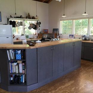 Große Maritime Wohnküche in L-Form mit flächenbündigen Schrankfronten, schwarzen Schränken, Arbeitsplatte aus Holz, Küchenrückwand in Weiß, Rückwand aus Holz, weißen Elektrogeräten, Korkboden und Kücheninsel in Burlington
