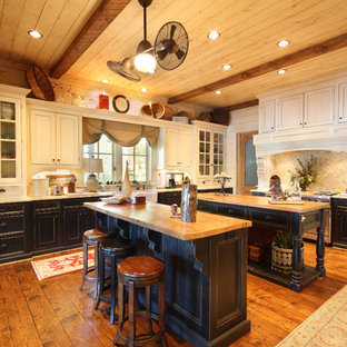 Enclosed kitchen - rustic l-shaped medium tone wood floor and brown floor enclosed kitchen idea in Atlanta with recessed-panel cabinets, black cabinets, wood countertops, beige backsplash, stone tile backsplash, a farmhouse sink, stainless steel appliances, two islands and beige countertops