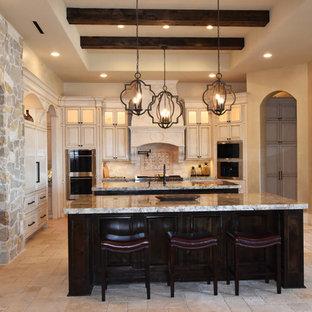 ヒューストンの大きい地中海スタイルのおしゃれなキッチン (アンダーカウンターシンク、レイズドパネル扉のキャビネット、ヴィンテージ仕上げキャビネット、御影石カウンター、ベージュキッチンパネル、石タイルのキッチンパネル、パネルと同色の調理設備、トラバーチンの床) の写真