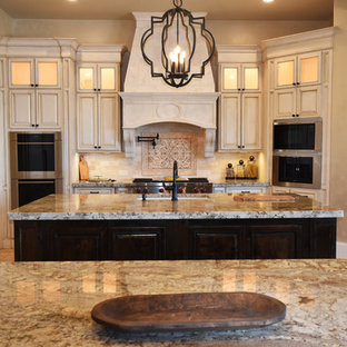 This is an example of an expansive mediterranean l-shaped kitchen pantry in Houston with a submerged sink, raised-panel cabinets, distressed cabinets, granite worktops, beige splashback, stone tiled splashback, integrated appliances, multiple islands and ceramic flooring.