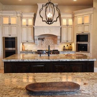 Geräumige Mediterrane Küche in L-Form mit Vorratsschrank, Unterbauwaschbecken, profilierten Schrankfronten, Schränken im Used-Look, Granit-Arbeitsplatte, Küchenrückwand in Beige, Rückwand aus Steinfliesen, Elektrogeräten mit Frontblende, zwei Kücheninseln und Keramikboden in Houston