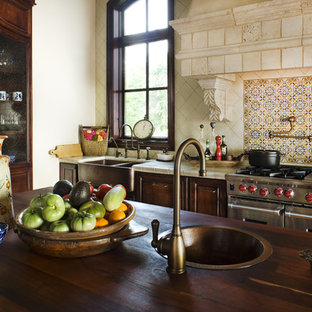 Photo of a country kitchen in Austin with stainless steel appliances, a farmhouse sink, tile benchtops and multi-coloured splashback.