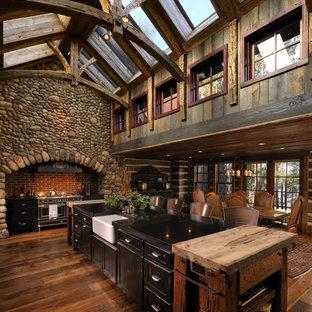 Immagine di una cucina abitabile rustica con lavello stile country, ante con riquadro incassato, ante con finitura invecchiata e elettrodomestici neri
