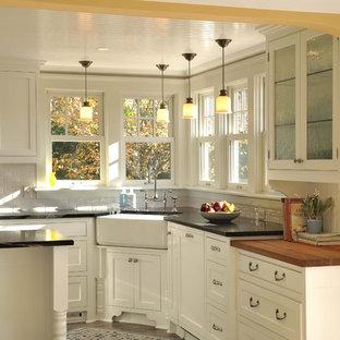 Diseño de cocina tradicional con salpicadero de azulejos tipo metro, fregadero sobremueble, armarios con rebordes decorativos, puertas de armario blancas y salpicadero blanco