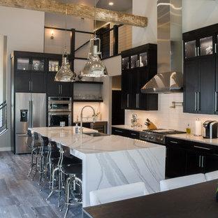 他の地域の広いインダストリアルスタイルのおしゃれなキッチン (エプロンフロントシンク、シェーカースタイル扉のキャビネット、黒いキャビネット、クオーツストーンカウンター、白いキッチンパネル、サブウェイタイルのキッチンパネル、カラー調理設備、淡色無垢フローリング、グレーの床、白いキッチンカウンター) の写真