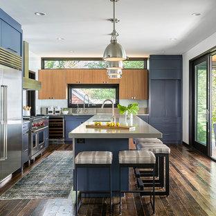 Источник вдохновения для домашнего уюта: угловая кухня в современном стиле с монолитной раковиной, плоскими фасадами, синими фасадами, столешницей из нержавеющей стали, техникой из нержавеющей стали, темным паркетным полом и островом