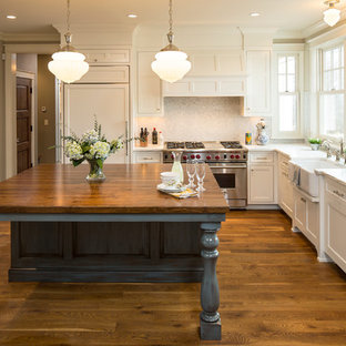 This is an example of a country kitchen in Minneapolis with marble benchtops.