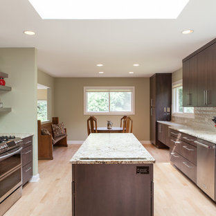 This is an example of a large contemporary galley kitchen/diner in Chicago with a built-in sink, flat-panel cabinets, brown cabinets, granite worktops, green splashback, ceramic splashback, stainless steel appliances, light hardwood flooring, an island, beige floors and multicoloured worktops.
