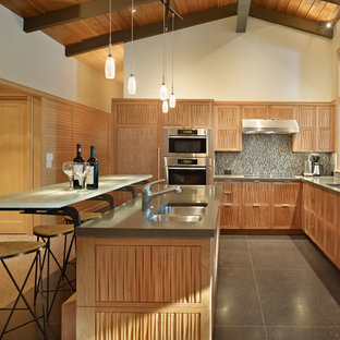 This is an example of a mid-sized midcentury l-shaped eat-in kitchen in Seattle with panelled appliances, a double-bowl sink, medium wood cabinets, quartz benchtops and with island.