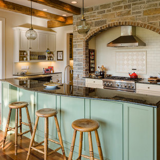 Rustic galley kitchen/diner in Raleigh with beaded cabinets, green cabinets, beige splashback, stainless steel appliances, medium hardwood flooring and an island.
