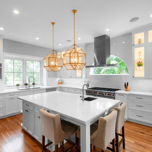 Transitional kitchen pictures - Transitional l-shaped medium tone wood floor and brown floor kitchen photo in Miami with a double-bowl sink, shaker cabinets, white cabinets, white backsplash, stainless steel appliances, an island and white countertops