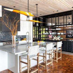 ミルウォーキーのビーチスタイルのおしゃれなキッチン (フラットパネル扉のキャビネット、白いキャビネット、アンダーカウンターシンク、黒いキッチンパネル、シルバーの調理設備の、オレンジの床、グレーのキッチンカウンター) の写真