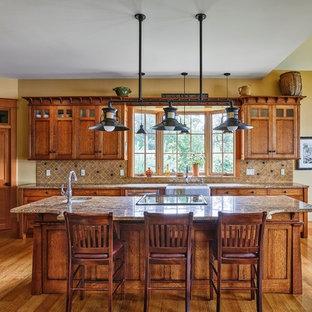 Foto di una cucina stile americano di medie dimensioni con lavello stile country, ante con riquadro incassato, ante in legno scuro, top in granito, paraspruzzi beige, paraspruzzi con piastrelle in pietra, elettrodomestici in acciaio inossidabile, parquet chiaro e isola