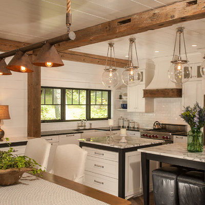 Mountain style l-shaped eat-in kitchen photo in New York with a farmhouse sink, shaker cabinets, white cabinets, granite countertops, white backsplash, subway tile backsplash and stainless steel appliances