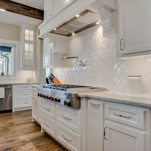 Inspiration for a large traditional u-shaped open plan kitchen in Dallas with a farmhouse sink, shaker cabinets, brown cabinets, quartzite benchtops, white splashback, ceramic splashback, stainless steel appliances, medium hardwood floors, with island, brown floor and white benchtop.