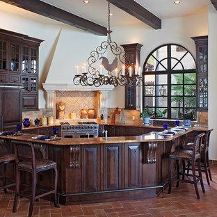 Imagen de cocina mediterránea con armarios tipo vitrina, electrodomésticos con paneles, puertas de armario de madera en tonos medios y salpicadero de piedra caliza