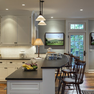 Traditional eat-in kitchen ideas - Elegant eat-in kitchen photo in New York with shaker cabinets, beige cabinets, stainless steel appliances and white backsplash