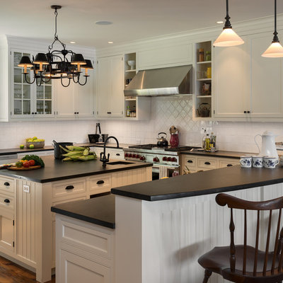 Elegant u-shaped kitchen photo in New York with a farmhouse sink, beaded inset cabinets, beige cabinets, white backsplash and stainless steel appliances