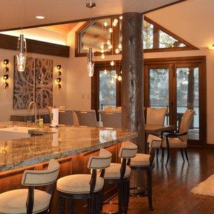 シアトルの中サイズのインダストリアルスタイルのおしゃれなキッチン (エプロンフロントシンク、インセット扉のキャビネット、中間色木目調キャビネット、御影石カウンター、マルチカラーのキッチンパネル、石タイルのキッチンパネル、シルバーの調理設備の、無垢フローリング、茶色い床) の写真