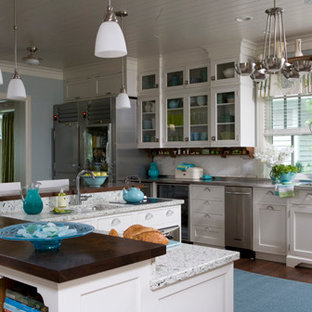 Photo of a large beach style kitchen in Other with an integrated sink, beaded inset cabinets, white cabinets, recycled glass benchtops, blue splashback, ceramic splashback, stainless steel appliances, dark hardwood floors, with island and brown floor.