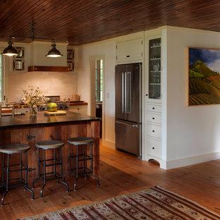 バーリントンの中くらいのラスティックスタイルのおしゃれなキッチン (エプロンフロントシンク、シェーカースタイル扉のキャビネット、中間色木目調キャビネット、ソープストーンカウンター、白いキッチンパネル、石タイルのキッチンパネル、シルバーの調理設備、淡色無垢フローリング) の写真