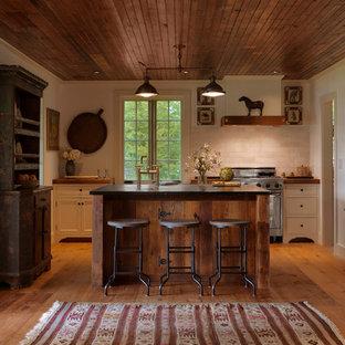 バーリントンの中サイズのラスティックスタイルのおしゃれなキッチン (シェーカースタイル扉のキャビネット、白いキャビネット、木材カウンター、白いキッチンパネル、石タイルのキッチンパネル、シルバーの調理設備の、無垢フローリング) の写真