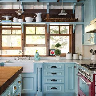 Idéer för lantliga kök, med en rustik diskho, luckor med infälld panel, blå skåp, färgglada vitvaror, mörkt trägolv och en köksö