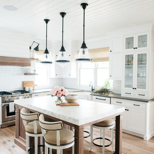 Mid-sized farmhouse eat-in kitchen ideas - Eat-in kitchen - mid-sized farmhouse u-shaped medium tone wood floor and brown floor eat-in kitchen idea in Detroit with a farmhouse sink, recessed-panel cabinets, white cabinets, marble countertops, white backsplash, subway tile backsplash, an island and gray countertops