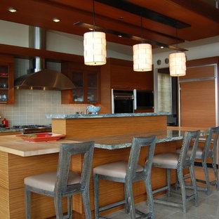 シアトルの大きいコンテンポラリースタイルのおしゃれなキッチン (アンダーカウンターシンク、フラットパネル扉のキャビネット、中間色木目調キャビネット、ライムストーンカウンター、グレーのキッチンパネル、セラミックタイルのキッチンパネル、パネルと同色の調理設備、トラバーチンの床、ベージュの床、緑のキッチンカウンター) の写真
