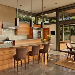 Modern eat-in kitchen in Seattle with beige splashback, glass tile splashback, stainless steel appliances, flat-panel cabinets and medium wood cabinets.