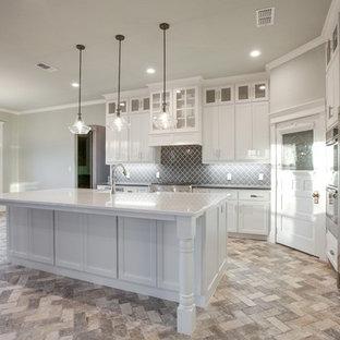 Inredning av ett klassiskt stort kök, med en rustik diskho, skåp i shakerstil, vita skåp, granitbänkskiva, grått stänkskydd, stänkskydd i glaskakel, rostfria vitvaror, tegelgolv, en köksö och grått golv