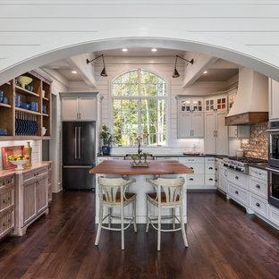Maritime Küche in L-Form mit Landhausspüle, Schrankfronten im Shaker-Stil, weißen Schränken, Küchengeräten aus Edelstahl, dunklem Holzboden, Kücheninsel, braunem Boden und schwarzer Arbeitsplatte in Sonstige
