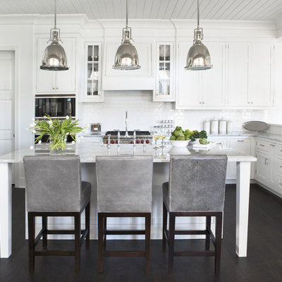 Kitchen - large traditional u-shaped dark wood floor kitchen idea in Other with stainless steel appliances, marble countertops, shaker cabinets, white cabinets, white backsplash, subway tile backsplash and an island