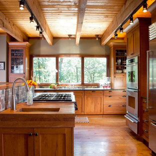 This is an example of a classic kitchen in Atlanta with stainless steel appliances, wood worktops, shaker cabinets and medium wood cabinets.