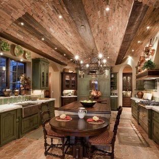 Large mediterranean u-shaped eat-in kitchen in Las Vegas with a farmhouse sink, raised-panel cabinets, green cabinets, with island, wood benchtops, green splashback, stone tile splashback, stainless steel appliances and terra-cotta floors.