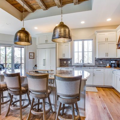 Eat-in kitchen - mid-sized rustic l-shaped medium tone wood floor and beige floor eat-in kitchen idea in Birmingham with shaker cabinets, white cabinets, granite countertops, an island, gray backsplash and stainless steel appliances
