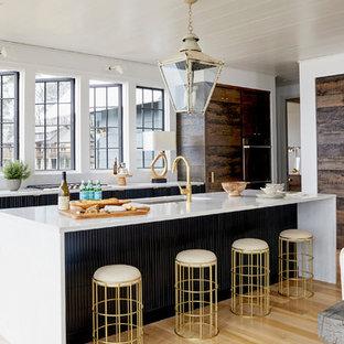 Imagen de cocina comedor en L, marinera, con fregadero bajoencimera, puertas de armario de madera en tonos medios, electrodomésticos con paneles, suelo de madera en tonos medios, una isla y suelo marrón