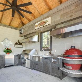 Foto di un'ampia cucina a L contemporanea con lavello stile country, ante a persiana, ante con finitura invecchiata, top in granito, elettrodomestici in acciaio inossidabile e pavimento in cemento