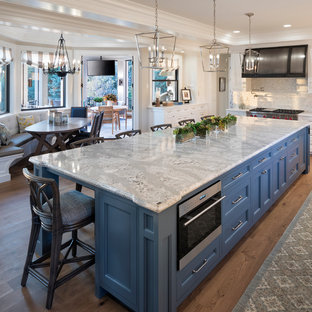 Huge traditional enclosed kitchen ideas - Example of a huge classic l-shaped dark wood floor and brown floor enclosed kitchen design in Minneapolis with a farmhouse sink, shaker cabinets, white cabinets, quartz countertops, white backsplash, marble backsplash, stainless steel appliances and an island