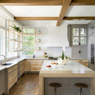 Farmhouse kitchen designs - Cottage u-shaped medium tone wood floor and brown floor kitchen photo in Minneapolis with an undermount sink, recessed-panel cabinets, gray cabinets, white backsplash, paneled appliances, an island, white countertops and window backsplash