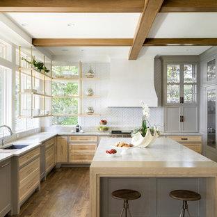 Foto på ett lantligt vit u-kök, med en undermonterad diskho, luckor med infälld panel, grå skåp, vitt stänkskydd, integrerade vitvaror, mellanmörkt trägolv, en köksö, brunt golv och fönster som stänkskydd