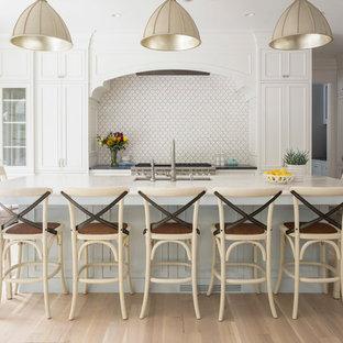 ミネアポリスの中サイズのビーチスタイルのおしゃれなキッチン (アンダーカウンターシンク、落し込みパネル扉のキャビネット、白いキャビネット、白いキッチンパネル、茶色い床、大理石カウンター、大理石の床、シルバーの調理設備の、淡色無垢フローリング) の写真